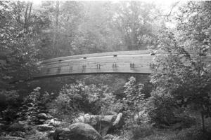 An arched wooden bridge spanning the Tye River on the Crabtree Falls Trail.