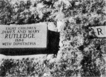 "James and Mary Rutledge and eight of their children, all died of diphtheria in 1884. [Names of the children are unknown.] The small ""R"" marker to the right is one of the eight markers noting children's graves."