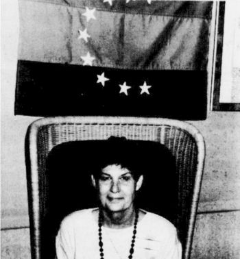 Cumberland's Governor, Jackie Epperson, sitting beneath the Cumberland State Flag.