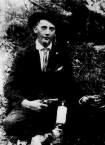 E.R. Bowman, Meadows of Dan, Virginia, about age 16 posed for this photo with gun and liquor bottles. Year is unknown. (Ella Boyd's photograph.)
