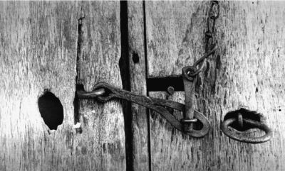 Notice detail of this hand made latch on the rough weather beaten boards of a barn door.
