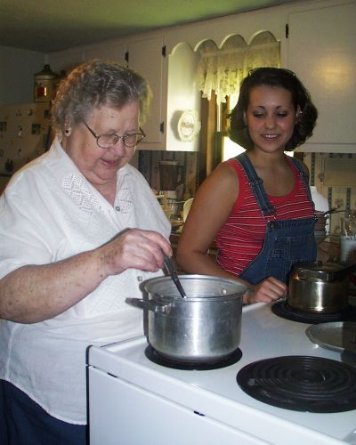 Mamie Crowder Adams giving her grandaughter, Brittany Gambill Dorman, a cooking lesson.