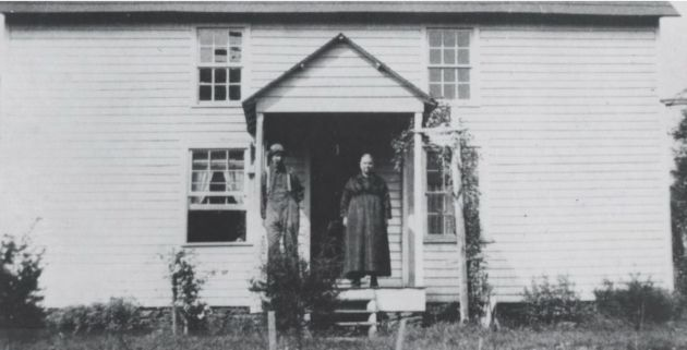 Image of Ed Mabry and his wife Lizzie in front of their house in the Mabry Mill area, near milepost 176.1 and section 1T of the Blue Ridge Parkway. The photograph shows the couple standing on the front stoop of their white clapboard home, which was built in 1915. The house was destroyed and replaced by the Matthews cabin, which was acquired by the National Park Service and restored and moved to the site in 1956. A copy of the original photograph was taken by Hugh Bell Muller in August of 1967. The original photograph was taken in 1922, and the original photographer is unknown.