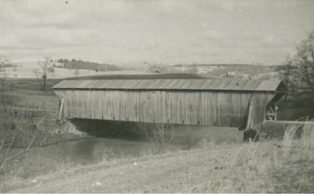 Image shows a covered bridge that crosses a stream. The walls of the bridge are made of wood, and the roof appears to be metal. The land beyond the bridge is relatively cleared of trees, and may be pasture or farmland. The image was taken near Floyd, Virginia, near milepost 162 and section 1R of the Blue Ridge Parkway.