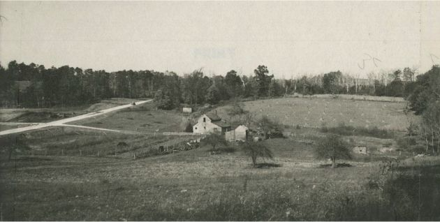 Image of a farmhouse and the surrounding land. On the left side of the image there is an automobile traveling along the Blue Ridge Parkway, as well as two parked vehicles. The image was likely taken near milepost 155 and station 987 in section 1Q of the Blue Ridge Parkway. Image taken by A. S. Burns on October 28, 1936.