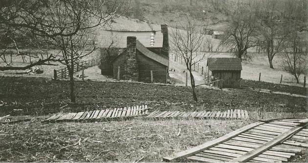 Image shows a house and a small shed at the center of a photograph taken looking down a hill. Possible wooden fence pieces lie on the ground in the foreground of the photograph. Fence posts and wooden fences run along the edges of the central house. The ground in the foreground appears to be primarily dirt and some grass and sticks. At the house and further in the background, the yard and hills beyond the house are covered in grass. There appear to be chickens in the yard to the right of the house. Scattered trees stand near the house and further in the background. Image taken near milepost 155.3 and station 100L in section 1R of the Blue Ridge Parkway, in Floyd County, Va. Image taken by Kenneth McCarter on March 20, 1940.