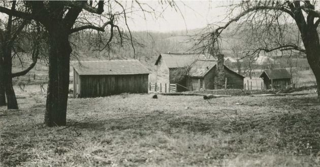 Image shows a dwelling, including a main house and two other small buildings, on a hill covered in grass. In the distance, to the right of the main house in center, is a series of at least three other buildings with white roofs. Image taken near milepost 155.3 and station 1001 in section 1R of the Blue Ridge Parkway, in Floyd County, Va. Image taken by Kenneth McCarter on March 20, 1940.