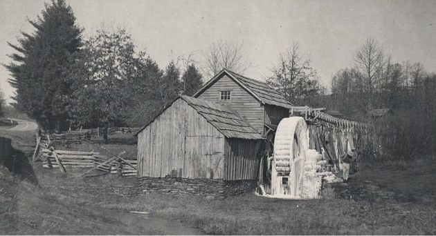 Image of Mabry Mill near milepost 176.1, section 1T of the Blue Ridge Parkway. The mill's water wheel is covered in snow and ice. The mill's flume can be seen extended from the rear of the mill to the elevated grounds behind the mill. The mill's stone base can also be seen in the image. Image taken from the National Park Service, Blue Ridge Parkway Headquarters. Photographer and date taken are unknown.