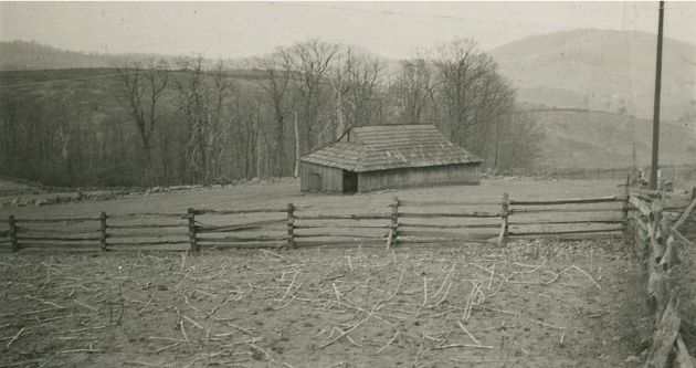 Image shows an old wooden barn, as seen from the Blue Ridge Parkway. In the foreground there is a stretch of open ground covered with scattered sticks or roots. A wooden fence runs along the center of the photograph, surrounding the barn and the grass-covered patch of land on which it sits. There appear to be stone fences in the background and to the left edges of the photograph, sectioning plots of land. A line of trees stands behind the fences, and rolling hills and mountains appear in the distance. Image taken by Robert G. Hall on March 28, 1939. Image taken to the right of VA Route 8, near milepost 165.4 in section 1S of the Blue Ridge Parkway.