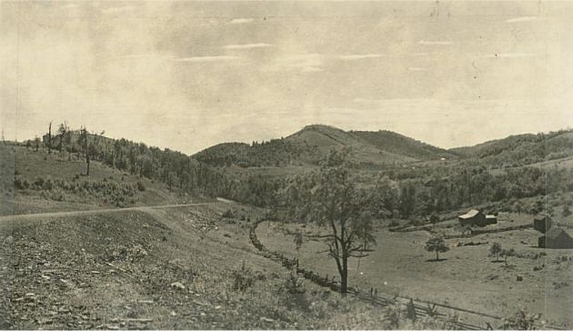 Image shows a valley, pasture, and possible farmhouse and farm buildings near the parkway. The road runs along the left side of the photograph, and the land slopes down to a valley below it on the right side. A wooden fence runs along the bottom of the valley, and an open pasture, farmhouse, and farm buildings appear in the right side of the image. Trees and rollings hills appear in the background beyond the farm buildings and the road. Image taken by Edward H. Abbuehl in May of 1938. Image taken somewhere between mileposts 165.4-174 in section 1S of the Blue Ridge Parkway, in the Rocky Knob Area in Patrick County and Floyd County, Va.